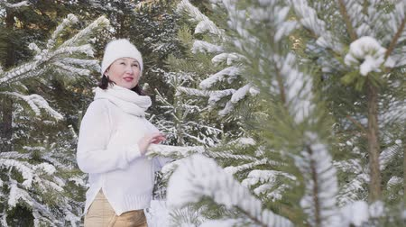 köknar ağacı : Beautiful smiling woman standing in snow-covered winter forest. Cheerful middle aged woman standing between evergreen trees covered with snow in scenic forest at wintertime Stok Video