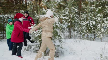 köknar ağacı : Happy family dancing around fir xmas tree in winter forest. Cheerful parents with adorable kids holding hands and dancing around snow-covered evergreen Christmas tree in forest at wintertime