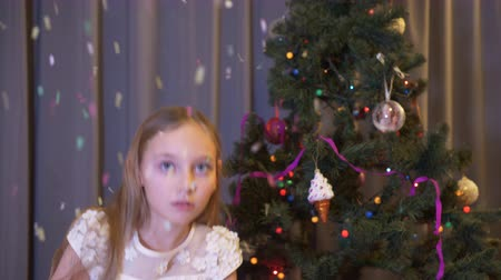 взрывной : Young girl blowing up cracker on Christmas tree background in living room. Scared girl teenager exploding flapper on New Year celebrate on decorative tree background