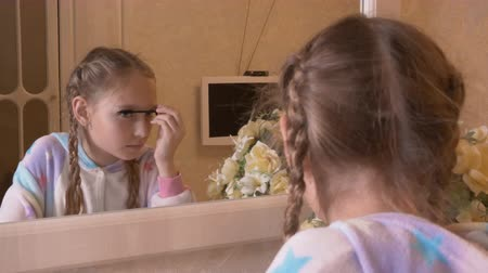 rozšíření : Girl teenager applying mascara on eyelashes front mirror in bedroom. Young girl using eyelashes mascara for makeup front bedroom mirror back view