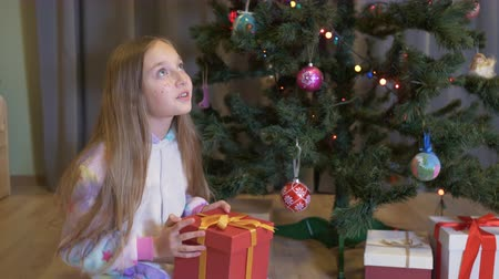 noel ağacı : Teenager girl opening red box with xmas New Year present on decorative tree background in living room. Happy girl looking present box with Christmas gift near holiday tree