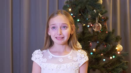 noel ağacı : Beautiful upset girl standing near christmas tree and crying indoors. Cute unhappy little girl standing near decorated christmas tree and crying at home