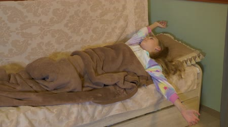 тахта : Cute little girl lying on bed and waking up. Adorable child in pajamas stretching arms and waking up at home Стоковые видеозаписи