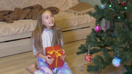 ajoelhado : Adorable little girl opening christmas present at home. Disappointed girl in pajamas sitting near christmas tree and opening gift box with socks