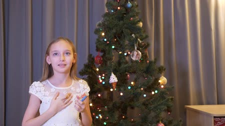 noel ağacı : Scared little girl banging with cracker indoors at christmastime. Adorable frightened, little girl holding festive cracker and standing near christmas tree at home