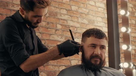 navalha : Portrait bearded man getting haircut in barbershop. Hairstylist cutting hair with electric razor in male salon. Close up face hipster man while hair dressing in barber salon