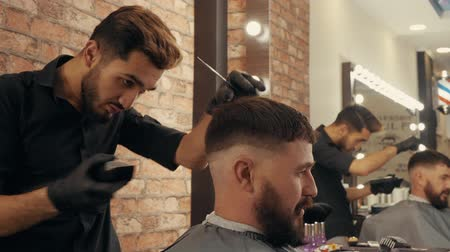 cavalheiro : Hair dresser using electric shaver for hair cutting bearded man in barber shop. Hairstylist using trimmer for brutal male hairdo. Male hairstyling with electric razor