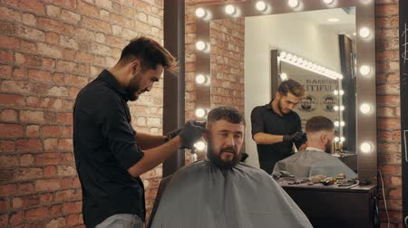grzebień : Hairdresser doing hair cut with hair machine for brutal man in barber shop. Barber making hairstyle with electrical shaver in male salon. Bearded man in barber shop