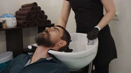 cavalheiro : Cropped shot of barber washing hair to bearded man in barbershop. Hairstylist in apron and gloves washing hair to serious handsome man above sink in barber shop