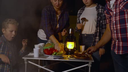 lampa naftowa : Tourist family eating barbeque bratwurst at dinner in forest hike in campsite. Mom, dad, son and daughter eating fried sausages on camping on tourist tent background