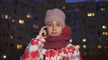 congelados : Teenager girl calling mobile phone at evening walk in winter street. Girl teenager talking smartphone on winter street in residential building background at dusk evening Archivo de Video