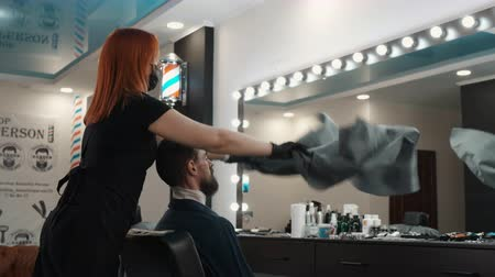 prádelník : Hair dresser dressing peignoir to bearded man before shaving in barber shop. Stylist using apron for hair cutting in male salon. Male hair care in beauty studio