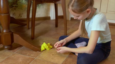 sprzątanie : Cute little girl cleaning floor and finding gold necklace. Adorable child wiping floor tiles with rag and finding golden chain indoors. Thoughtfurl face