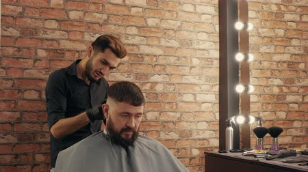 bigode : Young hairdresser talking and trimming hair to handsome male client. Smiling young barber holding electric clipper and grooming bearded man in barber shop Stock Footage