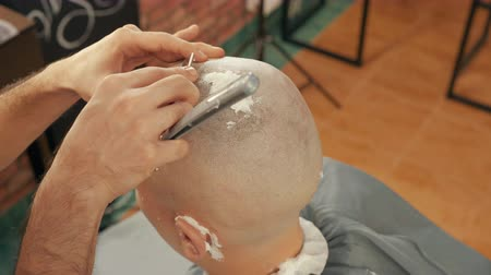 bigode : Cropped shot of barber shaving head of client with straight razor. Close-up partial view of hairdresser holding blade and shaving head of male client with foam in barber shop Stock Footage