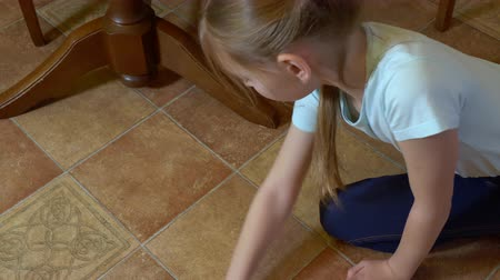 sprzątanie : Young girl wiping tiled floor with rag in kitchen. Housewife mopping with rag kitchen floor while homework overhead view