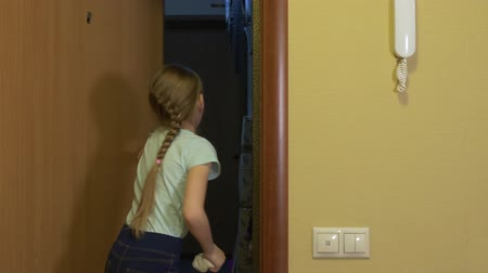 girmek : Cute teenage girl opening and closing door for her friend. Adorable child holding and playing with slime while closing door after friend with backpack at home