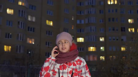 chapéu : Cute teenage girl walking outdoors and talking by smartphone in evening. Low angle view of adorable child in winter clothing, scarf and hat walking on street and talking by mobile phone in darkness