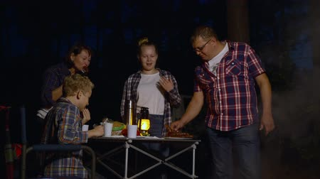 lampa naftowa : Happy family eating grilled sausages in camping in the evening. Middle aged parents with teenage kids eating meat while gathering around table at campsite in darkness