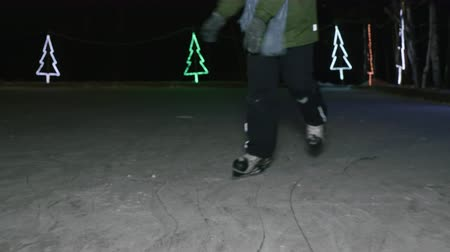 skate : Low section of child skating on ice in the evening at wintertime. Cropped shot of child in skates skating on skating ring in darkness at winter night Stock Footage