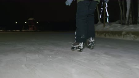 bruslař : Male legs in ice skates skating on night ice rink in winter park. Boy feet riding on skates on winter rink in night back view from low angle