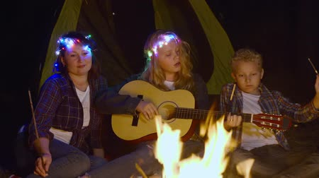 filha : Teenager girl playing on guitar and singing song front campfire in forest hike. Friendly family singing song at camping near bonfire campsite. Teenager girl playing guitar for family