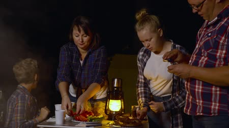jíst : Tourist family eating bbq sausage and vegetables at evening dinner in summer camping at dark. Traveling family dining roasted food at campsite in forest hike