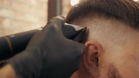 grzebień : Close up barber stylist using hair trimmer for male hairstyle. Male haircut with electric shaver. Hair dressing in barber shop. Hairdresser cutting hair with electric razor