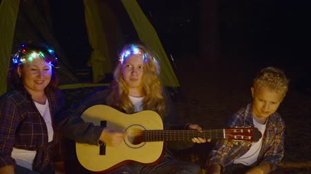 filha : Cheerful girl playing guitar music and singing song together mom and brother family front campfire in night forest. Girl playing music on guitar and singing for family front bonfire in summer hike