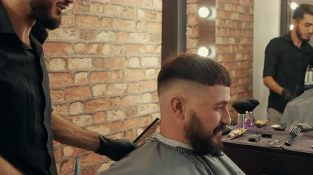 hairstyliste : Male stylist taking barber scissors for male cutting in beauty salon. Hipster man receiving stylish haircut in barber shop. Barber shaving male hair with electrical razor Stockvideo
