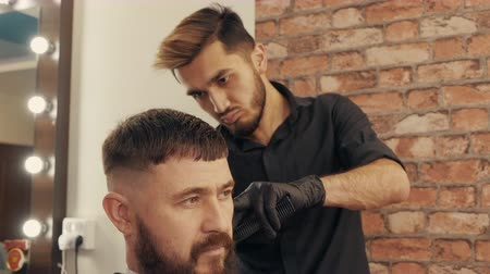 grzebień : Portrait bearded man getting male haircut in barber shop. Barber cutting hair with electrical shaver and comb in barber shop. Hipster man cutting hair in trendy male salon Wideo