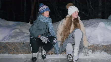 patenci : Teenager boy and girl resting after skating on ice rink snow at winter evening in park. Girl and boy in skates sitting in outdoor winter rink after skating.