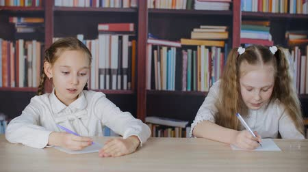 hazugság : Schoolgirls writing from cheat sheet on school exam at bookcase background. Two student girl solving task with cheat sheet at school test in class on bookshelf background
