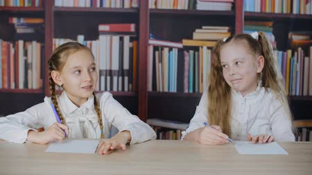 koncentracja : Smiling schoolgirl solving task at school exam on bookshelf background. Happy classmate writing test at school lesson in classroom with bookcase