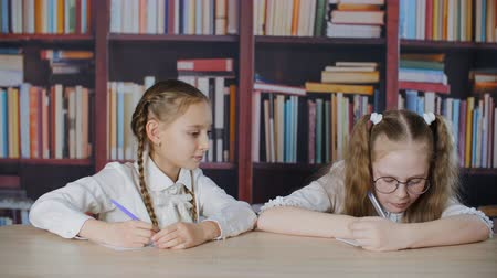 hazugság : Schoolgirl copying solution from classmate at exam in school on bookcase library background. Tricky student girl peeking test answer in cheat sheet in classroom Stock mozgókép