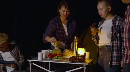 kiełbasa : Family eating grilled sausages in camping at night time. Parents and teenage kids spending time together and eating grilled meat with vegetables in campsite in the evening