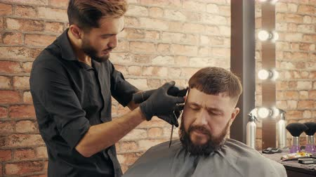 hairstyliste : Young barber grooming handsome male client in barbershop. Focused hairdresser holding electric clipper and trimming hair to handsome bearded man in barber shop