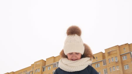 nyomott : Sad little girl standing on street and looking down at wintertime. Low angle view of upset child in winter clothes crying and looking for something outdoors during daytime Stock mozgókép