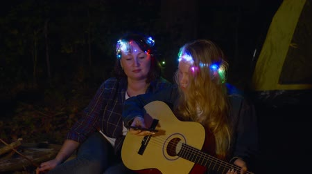 garlands : Beautiful women with smartphone and guitar in camping at nighttime. Attractive women with illuminated colorful garlands on heads sitting together and enjoying acoustic guitar in camp at night