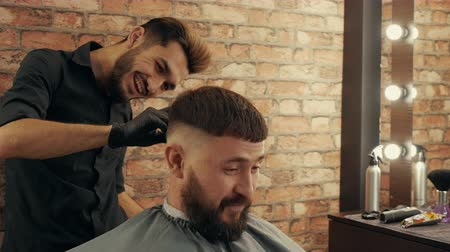 shaver : Happy bearded man talking with hairdresser in barbershop. Smiling young barber grooming handsome cheerful client in barber shop Stock Footage