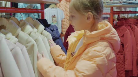 seçme : Teenager girl choosing jacket in fashion showroom. Young woman looking clothes in shop. Girl teenager shopping in clothes store Stok Video