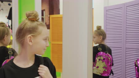 seçme : Teenager girl trying fashion backpack front mirror in fashion boutique at shopping. Happy young girl looking new backpack in shopping store front mirror
