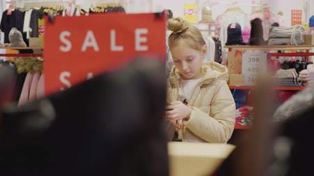 koopjes : Girl shopping at sale. Teenager girl using mobile phone while shopping in clothes store. Young woman holding smartphone while choosing clothes in fashion boutique. Stockvideo