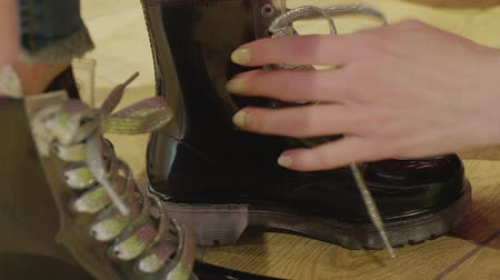 торг : Cropped closeup female hands tying shoelaces on black boots in shopping centre close up. Hands seller tie shoelaces in black shoes for buyer while trying in fashion showroom