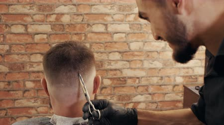 mestre : Hair dresser using scissors for hair cutting in barber shop. Hairstylist doing male hairdo with scissors. Male hairstyling with barber accessories close up.