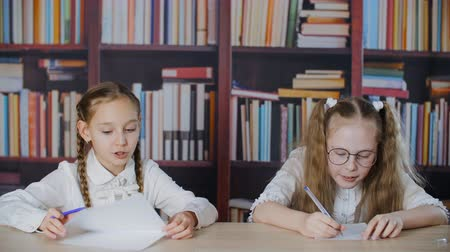 книжный шкаф : Two school girl speaking at table in classroom with bookshelf on background. Happy teenager girl classmates talking at desk on bookcase background