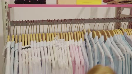 barganha : Female hands touching hangers with shirts in clothes showroom. Seller arranging hangers with clothes in fashion boutique in shopping centre Stock Footage