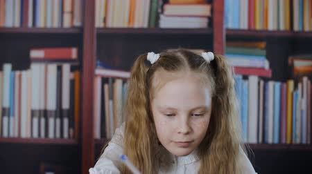Freckled schoolgirl writing on bookshelf background. Portrait smiling student girl writing homework in classroom on bookcase background Stock Footage