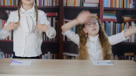 basisschool : Cute happy playful schoolgirls dancing at desk in library. Two adorable cheerful girls having fun together in classroom