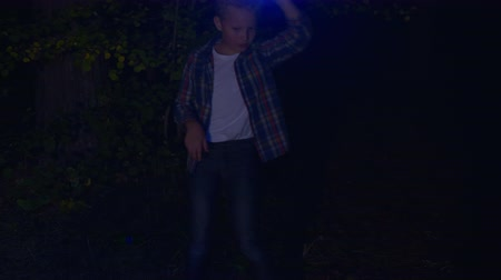 dyskoteka : Teenager boy dancing with light in dark forest. Young boy with flashlight dancing in night forest at dark